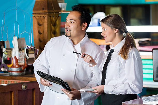 Chef And Waitress Talking Near Commercial Kitchen In Restaurant